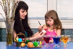 Lilla flickan med mamman målar påskägg för ferien Royaltyfri Bild