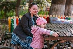 Lilla flickan med modern i parkerar royaltyfri bild