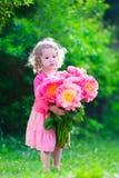 Lilla flickan med pionen blommar i trädgården Royaltyfri Fotografi