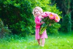 Lilla flickan med pionen blommar i trädgården Arkivbilder