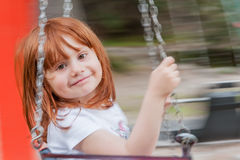 Lilla flickan med rött hår ler på gungan Arkivbilder