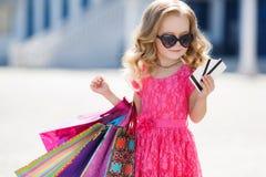 Lilla flickan med shoppingpåsar går till lagret Arkivfoton