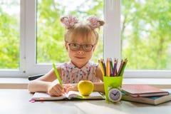 Lilla flickan med skolatillförsel sitter på tabellen arkivbild