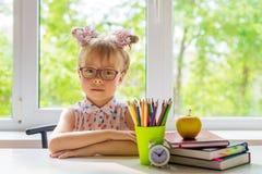 Lilla flickan med skolatillförsel sitter på tabellen royaltyfria foton