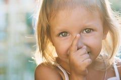 Lilla flickan med stora härliga ögon pekar uppåt royaltyfria bilder