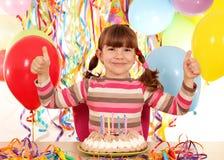 Lilla flickan med tummar up födelsedagpartiet Arkivbilder