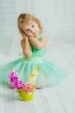 Lilla flickan med våren blommar i vas Arkivfoton