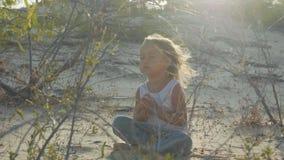 Lilla flickan mediterar på öknen Barnsammanträde på sanden på den varma solnedgången lager videofilmer