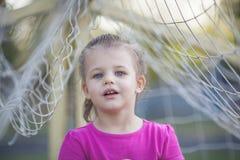 Lilla flickan mellan fotboll förtjänar Arkivfoton