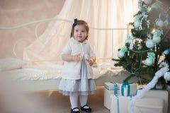 Lilla flickan nära julgranen med gåvor jublar ferie, det nya året, garneringar, gåvan, asken, ferie, livsstil Royaltyfria Bilder