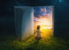 Lilla flickan och öppnar boken Arkivbild