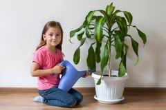 Lilla flickan och blått som bevattnar kan Arkivfoto