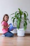 Lilla flickan och blått som bevattnar kan Royaltyfri Foto