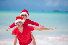 Lilla flickan och den lyckliga fadern i Santa Hat under strandjul semestrar fotografering för bildbyråer