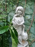 Lilla flickan och en and skulpterar och gör grön den på engelska trädgården för vinrankan Arkivbild