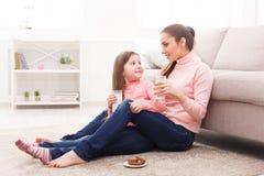 Lilla flickan och hennes dricka för mamma mjölkar hemma fotografering för bildbyråer