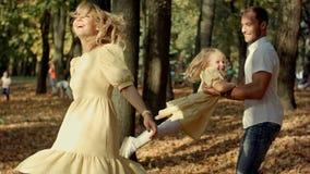 Lilla flickan och hon föräldrar som spelar i hösten, parkerar arkivfoto