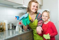 Lilla flickan och mamman ordnar på kök arkivbild
