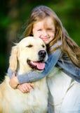 Lilla flickan omfamnar golden retriever i parkera Arkivfoto