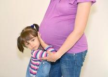 Lilla flickan omfamnar händer en mage av den gravida modern Arkivbild