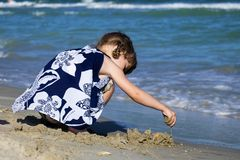 Lilla flickan på stranden av havet bygger en sandslott royaltyfri bild
