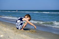Lilla flickan på stranden av havet bygger en sandslott fotografering för bildbyråer