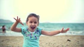 Lilla flickan på stranden, lyckligt litet behandla som ett barn att spela med sand på stranden Ett barn, ett barn, barn, sinnesrö arkivfilmer
