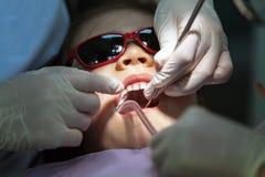 Lilla flickan på tandläkaren Chair, unge tar tand- tillvägagångssätt royaltyfria bilder