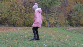 Lilla flickan parkerar in höst Förtjusande liten flickaleenden arkivfilmer