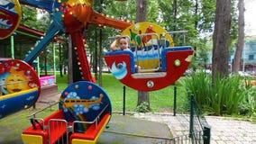 Lilla flickan rider en karusell Parkera av dragningar stock video