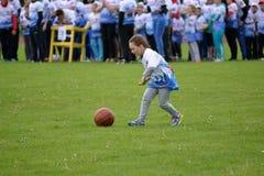 Lilla flickan rullar för henne en boll med hjälp av en pinne på de gladlynta starterna för konkurrenser Royaltyfria Bilder