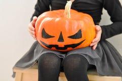 Lilla flickan rymmer en läskig pumpa för allhelgonaafton som sitter på en bänk Closup arkivbild