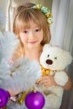 Lilla flickan rymmer en nallebjörn i hennes hand nära en vit Fotografering för Bildbyråer