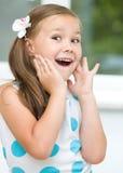 Lilla flickan rymmer hennes framsida Arkivfoton