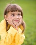 Lilla flickan rymmer hennes framsida Arkivbild
