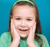 Lilla flickan rymmer hennes framsida Arkivfoto