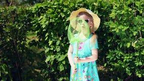 Lilla flickan rymmer skopa-netto på bakgrund av gröna buskar i sommar stock video