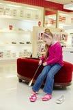 Lilla flickan sätter på skon som hjälper sig vid skohornet Arkivfoton