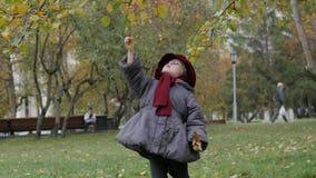Lilla flickan samlar höstlövverk i parkera Royaltyfri Bild