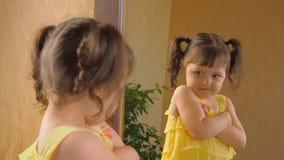 Lilla flickan ser i spegeln En härlig flicka med svansar på hennes huvud exponerar ett öga Ett barn i a