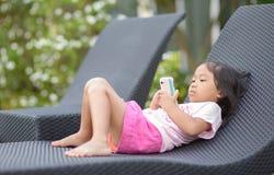 Lilla flickan ser på mobiltelefonen royaltyfri bild
