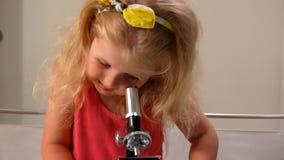 Lilla flickan ser rolig till och med ett mikroskop lager videofilmer
