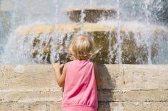 Lilla flickan ser springbrunnen arkivbild