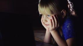 Lilla flickan ser tecknade filmen på bärbara datorn Den lysande bärbar datorskärmen exponerar framsidan för barn` s stock video