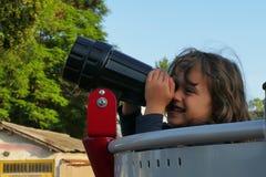 Lilla flickan ser till och med ett teleskop royaltyfri foto