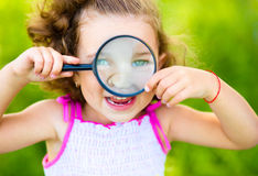 Lilla flickan ser till och med förstoringsapparaten arkivfoto