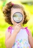 Lilla flickan ser till och med förstoringsapparaten arkivbilder