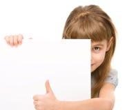 Lilla flickan ser ut från det tomma banret Arkivbild