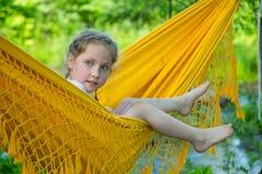 Lilla flickan ser ut ur hängmattan arkivfoton