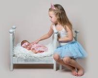 Lilla flickan sitter därefter hennes nyfödda syster arkivbilder